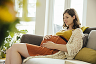 Pregnant woman holding her baby belly while relaxing on couch at home - MFF001785