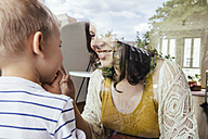 Mother and son making contact through a window - MFF001793