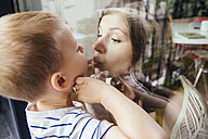 Mother and son kissing through a window - MFF001794