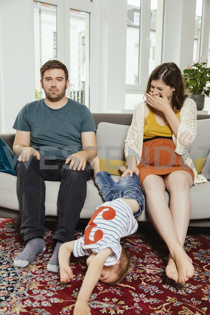 Disturbed family portrait on a sofa at home with son jumping away - MFF001799