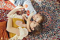 Mother and little son cuddling on a Persian rug at home - MFF001801