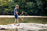 Boy playing with wooden toy boat at a river - LVF003622
