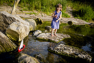 Little girl playing with wooden toy boat at riverside - LVF003626