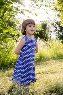Portrait of little girl standing in hay field - LVF003631