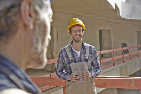 Smiling man with hard hat on construction site - FMKF001591