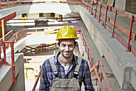 Smiling man with hard hat on construction site - FMKF001596