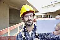Smiling man with hard hat on construction site taking a selfie - FMKF001599