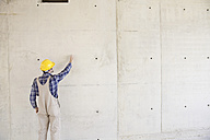 Man with hard hat on construction site drawing on concrete wall - FMKF001602