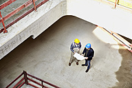 Construction worker and architect with plan talking on construction site - FMKF001605