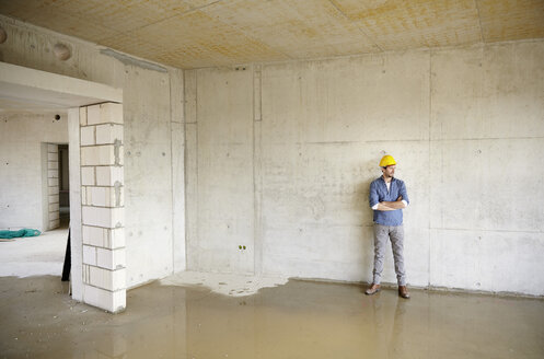 Man on construction site standing at large puddle - FMKF001627