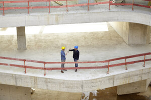 Two men with hard hats clinking beer bottles on construction site - FMKF001632