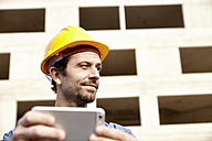 Man with hard hat on construction site holding cell phone - FMKF001634
