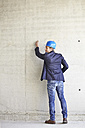Man with hard hat on construction site drawing on concrete wall - FMKF001641