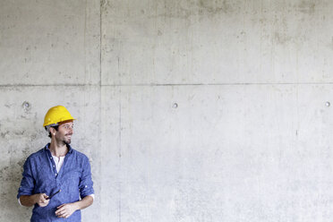 Smiling man with hard hat on construction site at concrete wall - FMKF001730