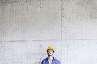 Man with hard hat on construction site at concrete wall looking up - FMKF001660