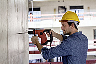 Man with hard hat on construction site using drill - FMKF001663