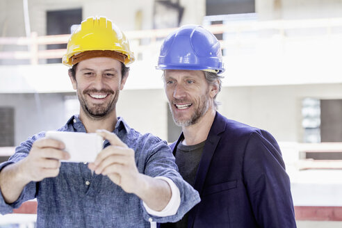 Two men on construction site taking a selfie - FMKF001666