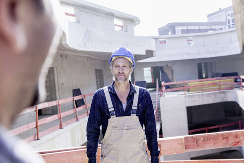 Confident man with hard hat on construction site - FMKF001674