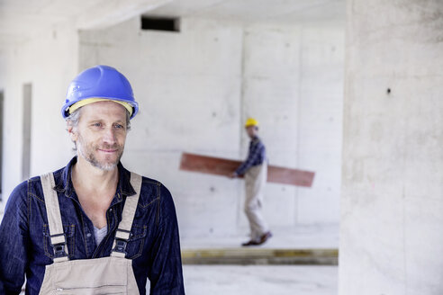 Smiling worker on construction site with colleague in background - FMKF001677