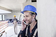Smiling worker on construction site on cell phone - FMKF001680