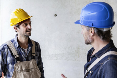 Two construction workers on construction site talking - FMKF001683
