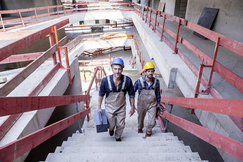 Two construction workers on construction site walking upstairs - FMKF001684