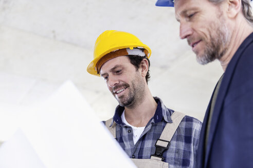 Construction worker and architect with plan talking on construction site - FMKF001687