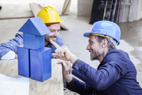 Two smiling men with hard hats and model house - FMKF001693