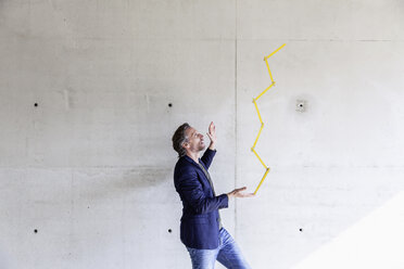 Man balancing poket rule in front of concrete wall - FMKF001696