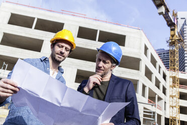 Two men on construction site looking at construction plan - FMKF001707