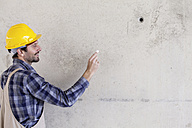 Man with hard hat on construction site drawing on concrete wall - FMKF001710