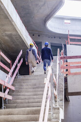 Construction worker and architect on construction site walking upstairs - FMKF001712