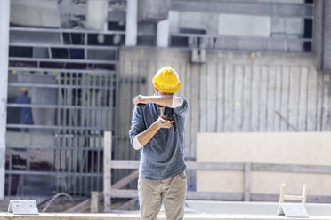 Man with cell phone wearing hard hat on construction site - FMKF001716