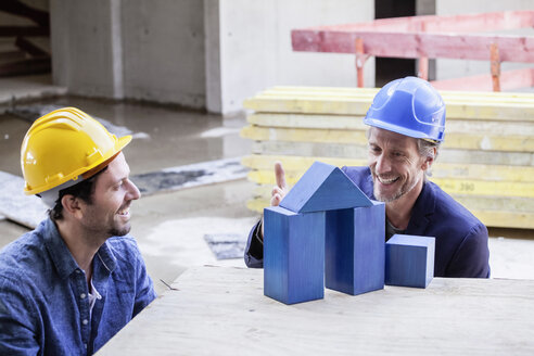 Two smiling men with hard hats and model house - FMKF001719