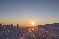 Germany, Saxony-Anhalt, Harz National Park, Brocken, rail tracks of Harz Narrow Gauge Railway in winter against the evening sun - PVCF000429
