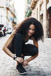 Spain, Barcelona, sportive young woman tying her shoe - EBSF000758