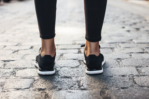 Black sneakers of sportive young woman, close-up - EBSF000760