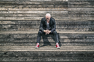 Businessman weraing suit and red sneakers sitting on wooden stairs - TAM000226