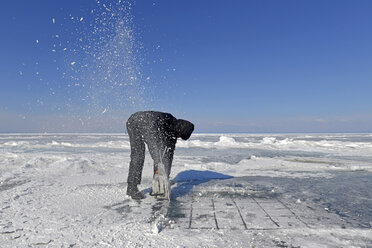 Russia, Lake Baikal, man opening an ice hole with a motor saw for ice diving - GN001347