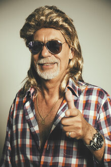 Portrait of smiling man wearing sunglasses and blond wig showing thumbs up - MFF001675