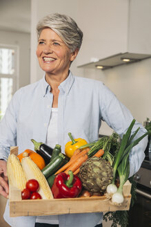 Portrait of woman holding wooden box of vegetables - MFF001740