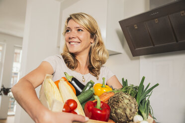 Portrait of young woman holding wooden box of vegetables - MFF001743