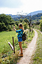 Alto Adige, teenage girl with backpack standing on a path taking a photo - GIOF000064