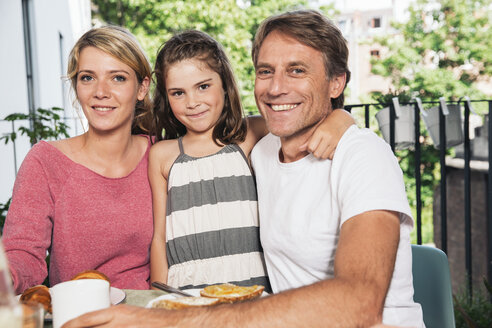 Smiling family sitting at breakfast table on balcony - MFF001701