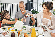 Three generations of family sitting at a large breakfast table on balcony - MFF001729