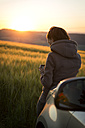 Germany, woman leaning on car in front of a field at sunrise - MIDF000493
