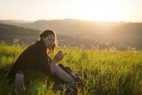 Germany, woman having breakfast on a meadow at sunrise - MIDF000496