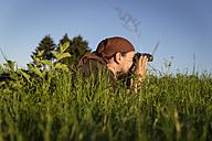 Germany, man lying on a meadow looking through binocular - MIDF000499