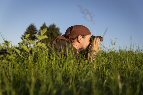 Germany, man lying on a meadow looking through binocular - MIDF000499