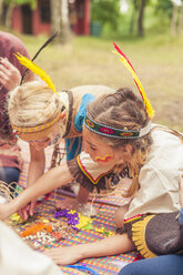 Germany, Saxony, Indians and cowboy party, Girls tinkering with beads - MJF001632